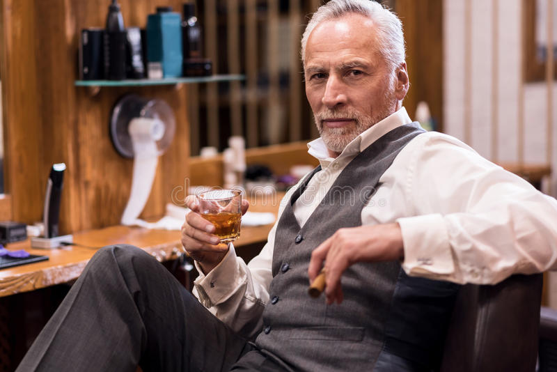 Man sitting with cognac glass and cigar. Expressing confidence, Attractive senior man wearing luxury suit sitting on leather armchair with cognac glass and cigar royalty free stock photo