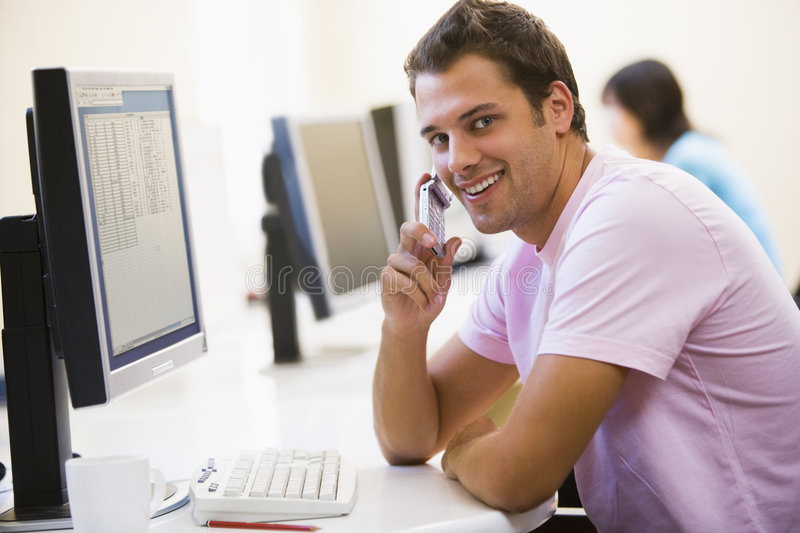 Man sitting in computer room using phone stock image