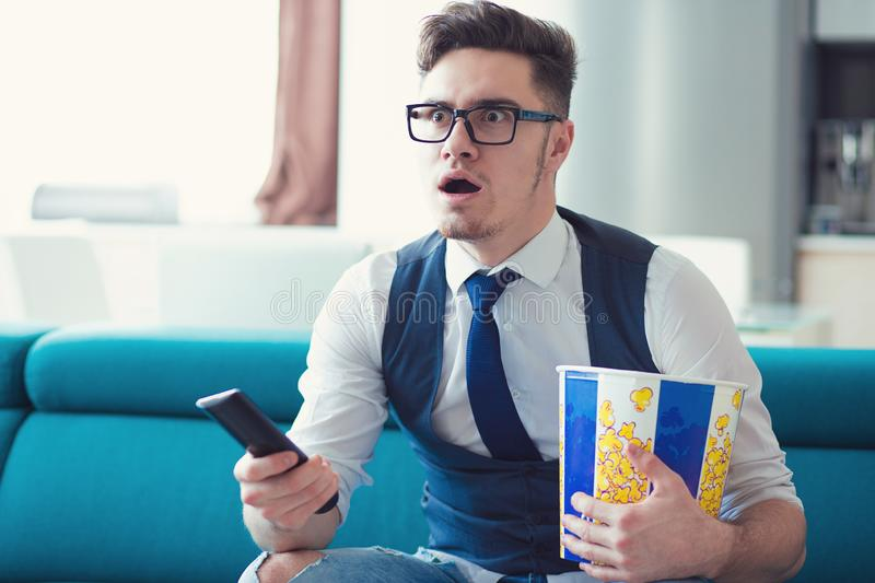 Man sitting on a couch, watching TV, holding remote and popcorn box, surprised at what he sees stock photo