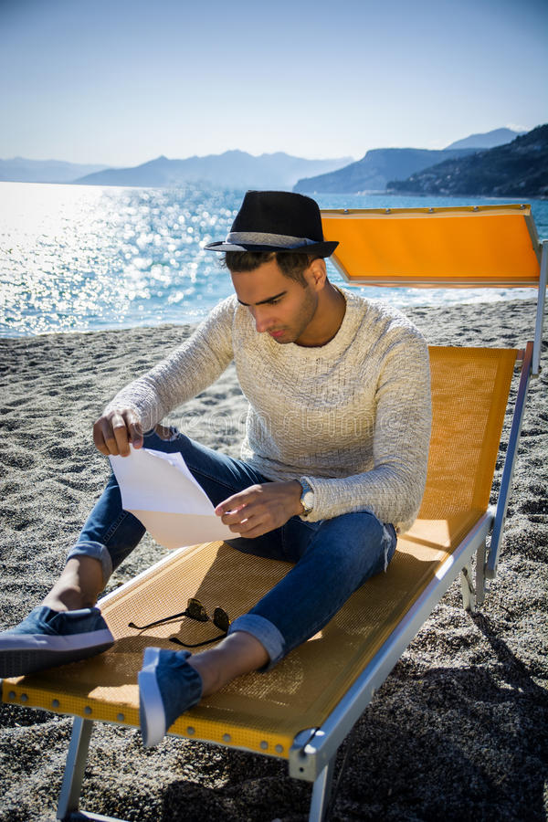 Man sitting on deckchair while reading letter. Young man on beach sitting on deckchair while reading letter. Seascape with hills on background stock photography
