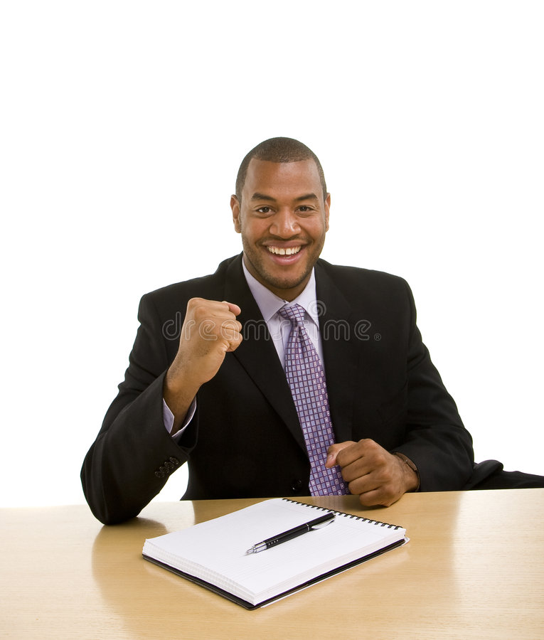 Man Sitting at Desk Closing Deal. A black businessman sitting at a desk with a pen and pad with triumphant look on his face royalty free stock images