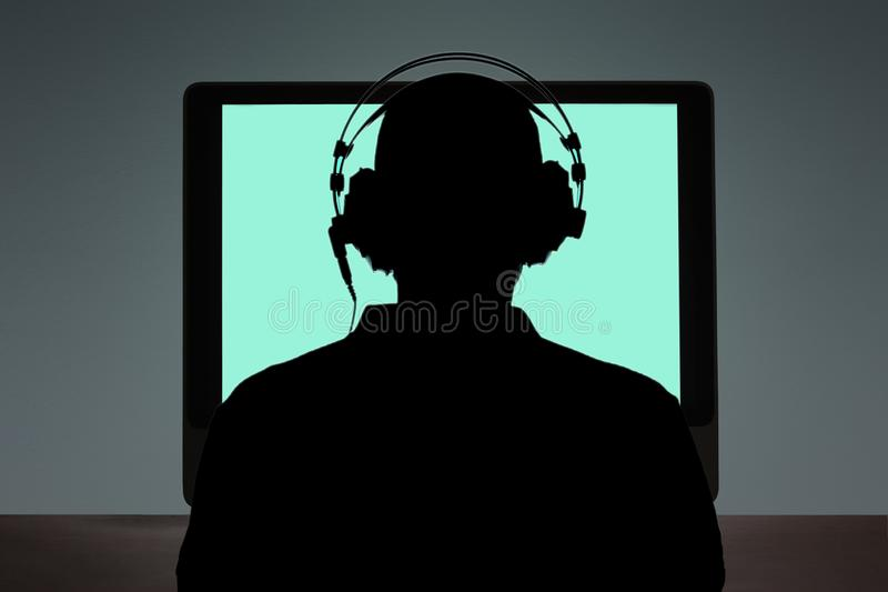 Man sitting at the desk in front of a computer with copy space for your text stock image