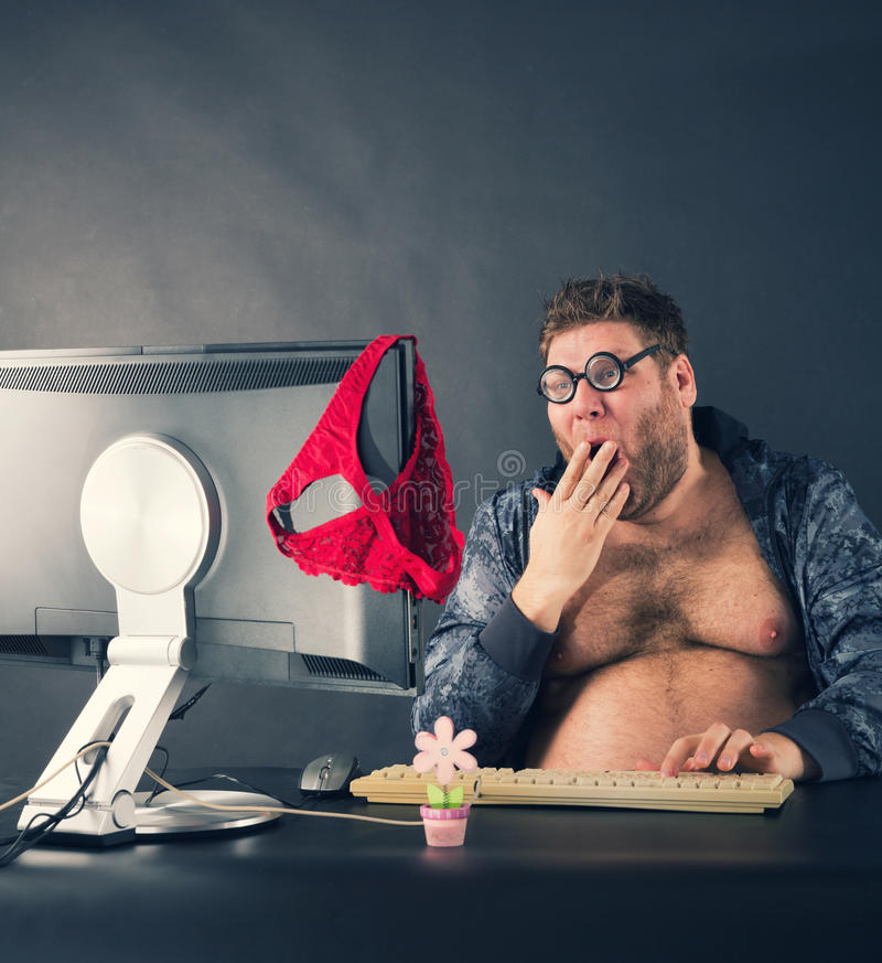 Man sitting at desk looking on computer screen. Fat funny man sitting at desk looking at computer screen royalty free stock image