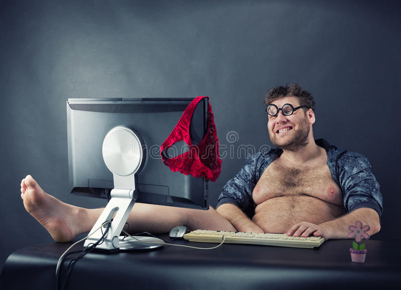 Man sitting at desk looking on computer screen. Fat smiling funny man sitting at desk looking at computer screen stock images