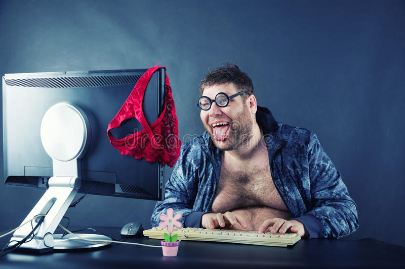 Man sitting at desk looking on computer screen. Fat smiling man sitting at desk looking at computer screen isolated on gray royalty free stock photo