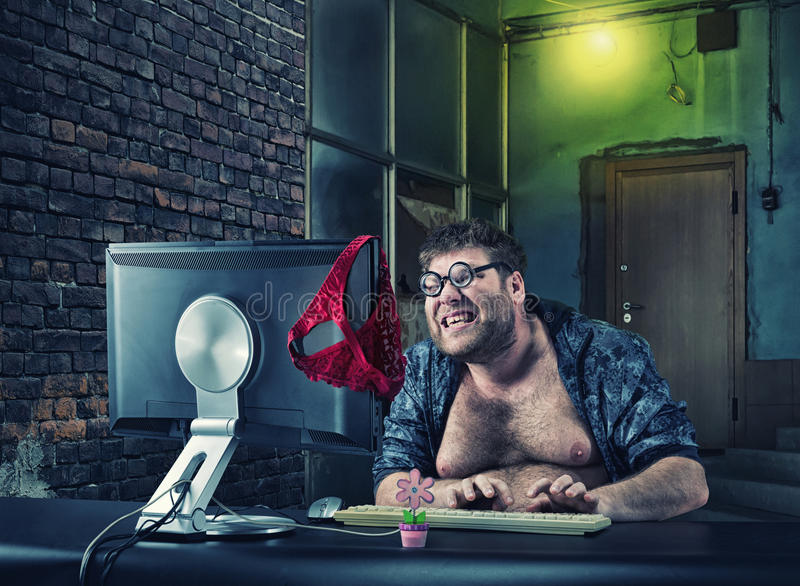 Man sitting at desk looking on computer screen. Fat smiling man sitting at desk looking at computer screen and writing to dating web stock photos