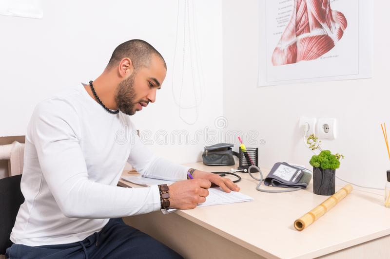 Man sitting at a desk writing notes in an office royalty free stock photo