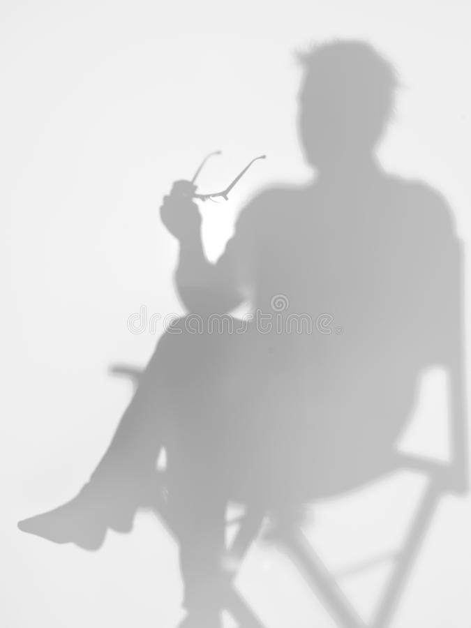 Man sitting on director s chair, silhouette