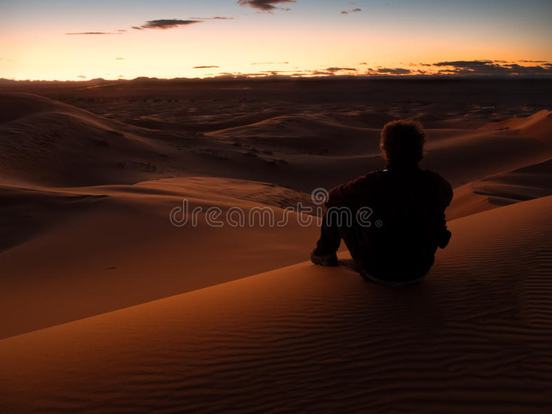 Man sitting on a dune in the desert while watching the sunset. royalty free stock photos