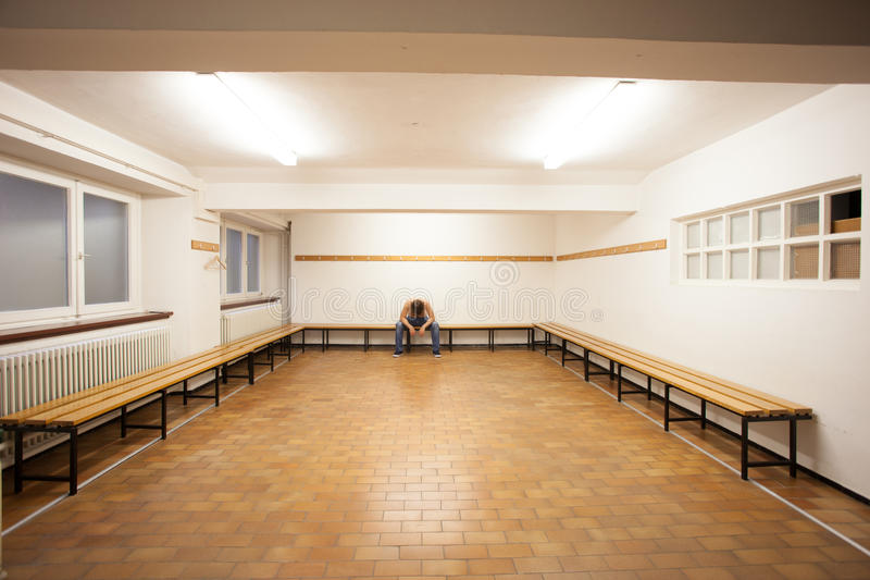 Man sitting in empty locker room. Man sitting in empty old locker room stock photos