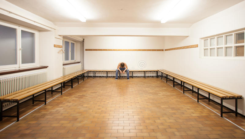 Man sitting in empty locker room. Man sitting in empty old locker room on bench stock images