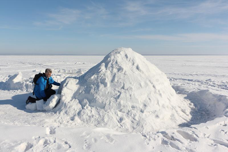 Man sitting at the entrance an igloo stock photography