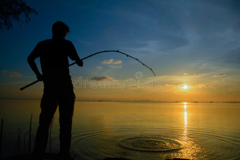 Man sitting on fishing At sunset. royalty free stock image