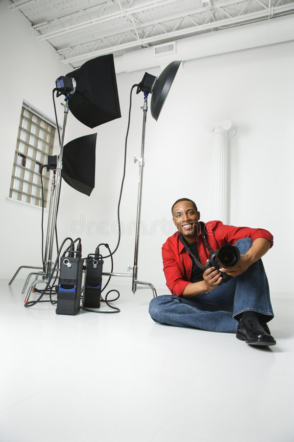 Man sitting on floor with camera. stock photography