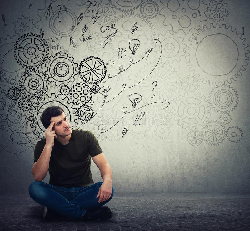 Man sitting on the floor hard thinking, find a solution to solve problem. Different imagination, alternative idea. Gear brain. Arrows and mess as thoughts stock image