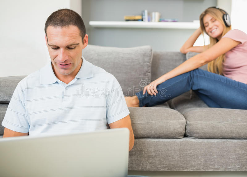 Man Sitting On Floor With Laptop With Woman Listening To Music O Stock Photo