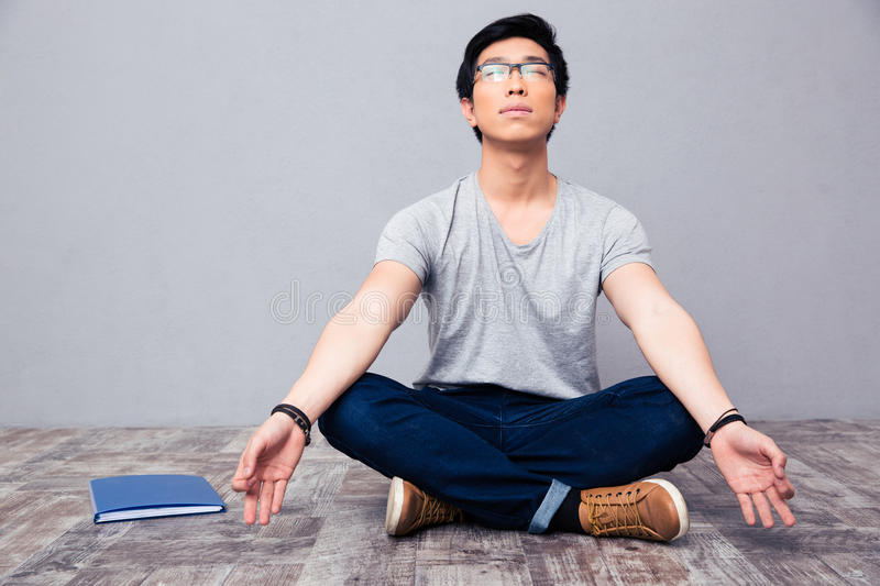Man sitting on the floor and meditating. Young asian man sitting on the floor and meditating stock photography