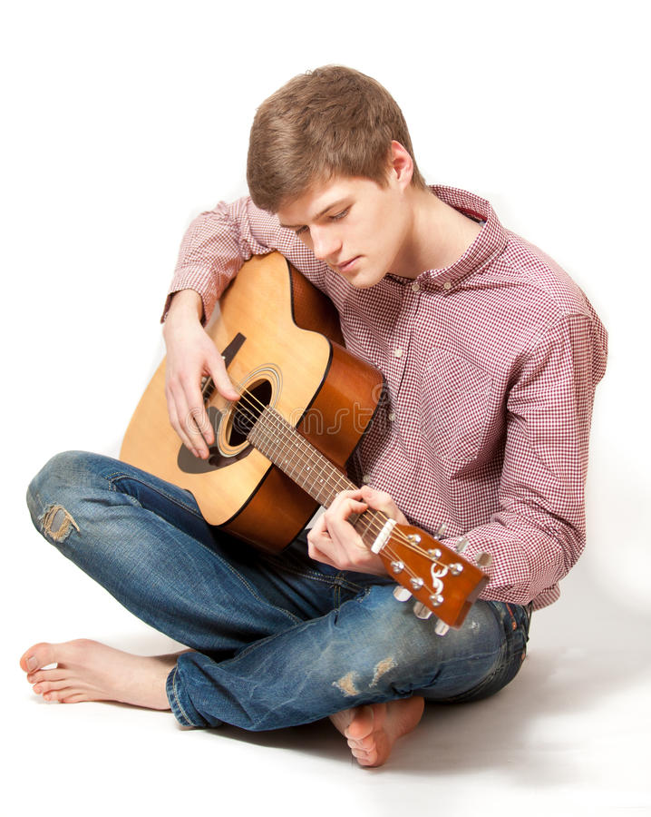Man sitting on floor and playing on classic guitar royalty free stock image