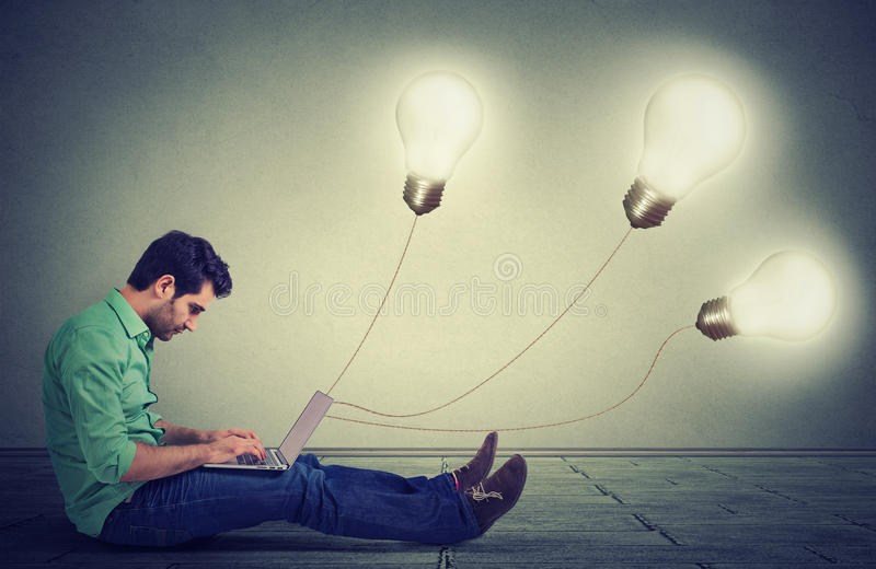 man sitting on floor using a laptop with many light bulbs plugged in it royalty free stock images