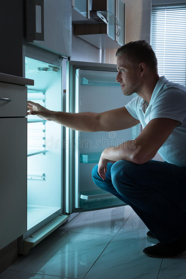 Man Sitting In Front Of Empty Fridge royalty free stock image