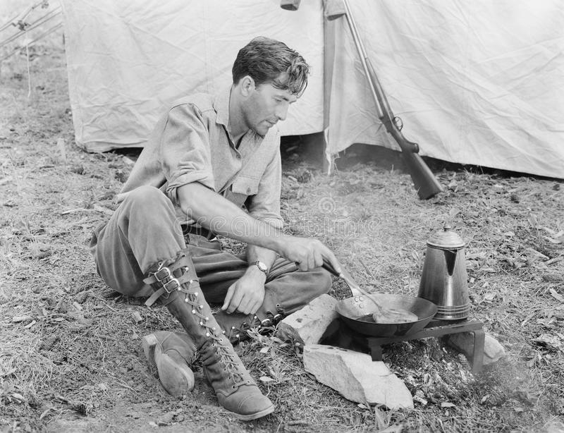 Man sitting in front of his tent preparing food royalty free stock images