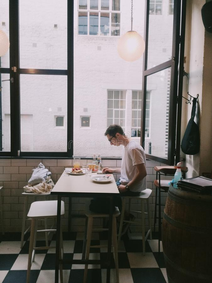 Man Sitting in Front of Table Holding Smartphone Beside Window royalty free stock photo