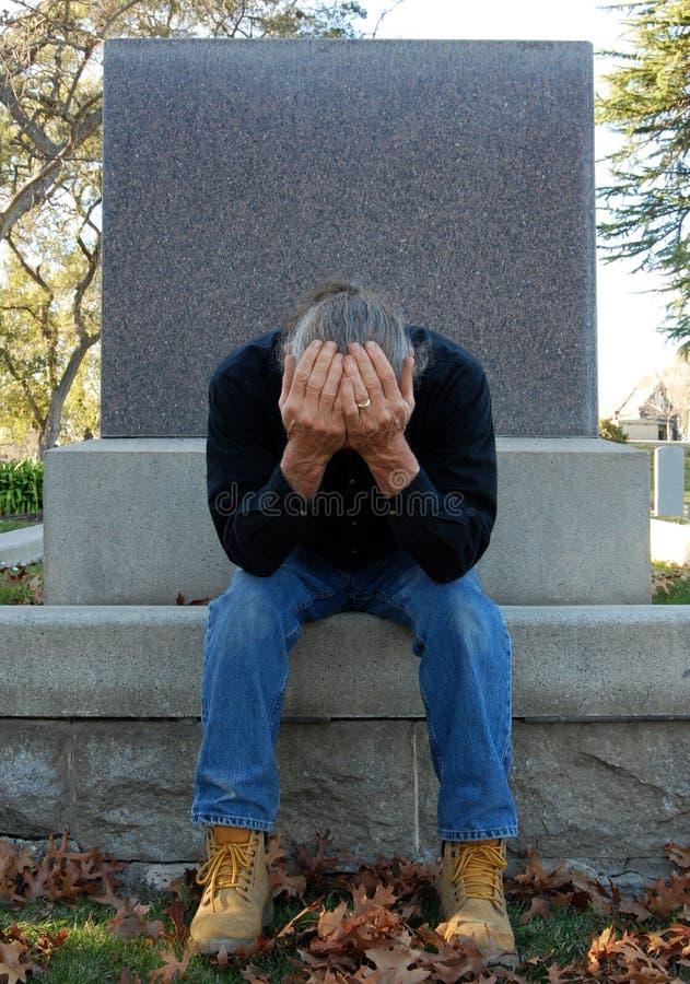 Man sitting at gravesite royalty free stock image