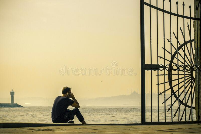 Man sitting at harbor royalty free stock photography