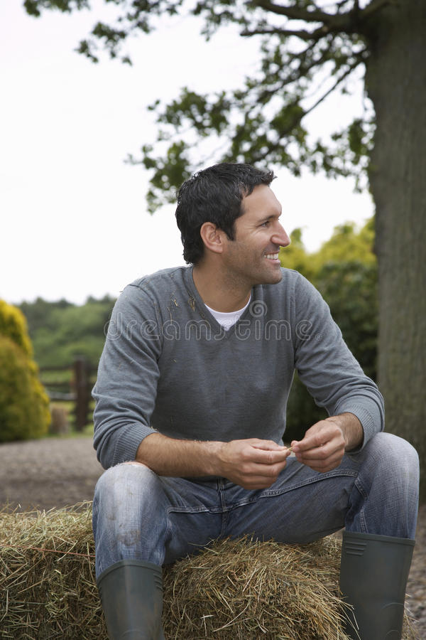 Man Sitting On Haybale Outdoors stock image