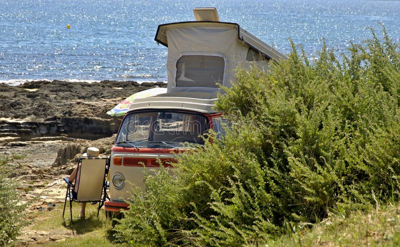 Campervan on the Mediterranean sea. A man is sitting beside his campervan enjoying the sun and the sea royalty free stock photos