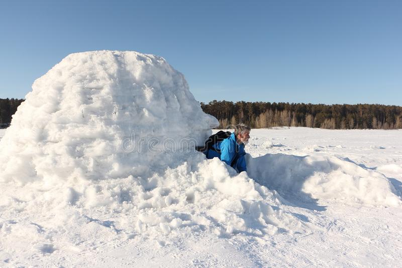 Man sitting in an igloo on the frozen reservoir. In winter stock photography
