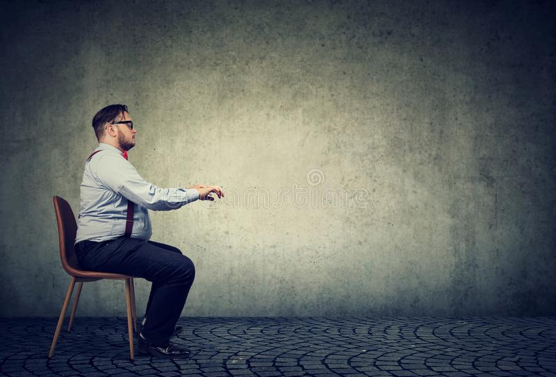 Man sitting at imaginary table stock images