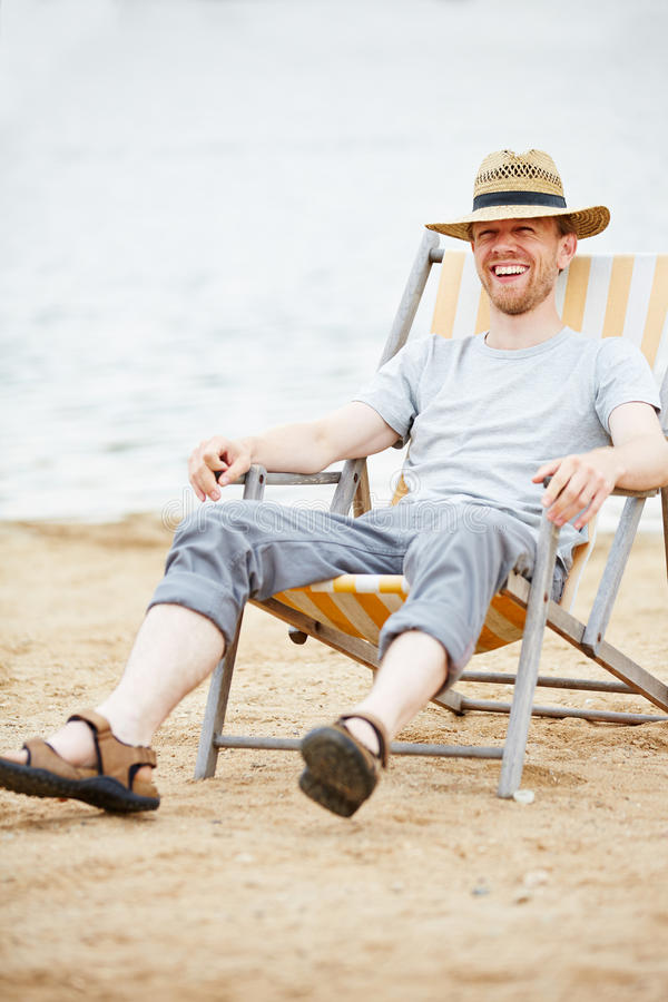 Free Man Sitting In Deck Chair On Beach Royalty Free Stock Photography - 55547647