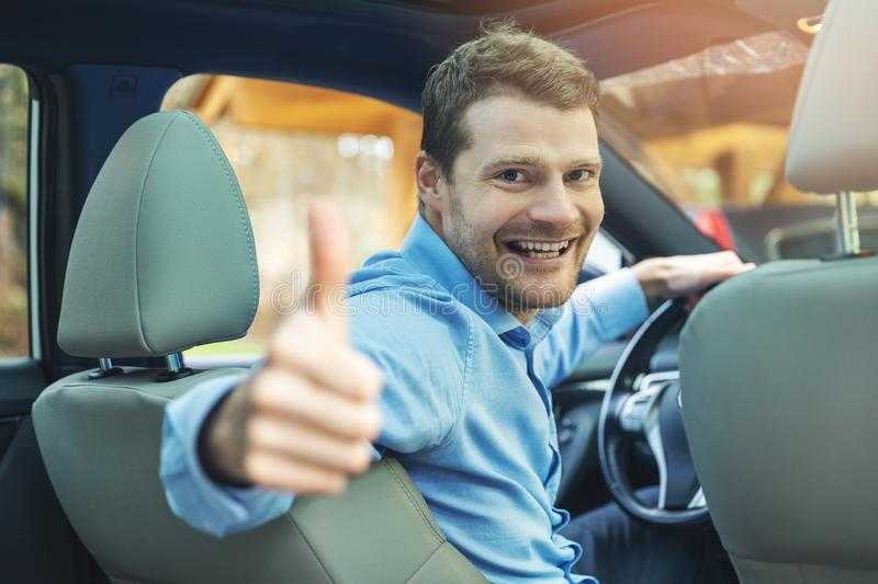 Man sitting inside the car and showing thumb up gesture royalty free stock images