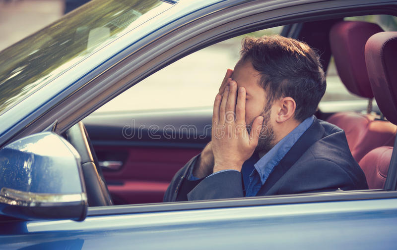Man sitting inside his car and feeling stressed and upset royalty free stock images