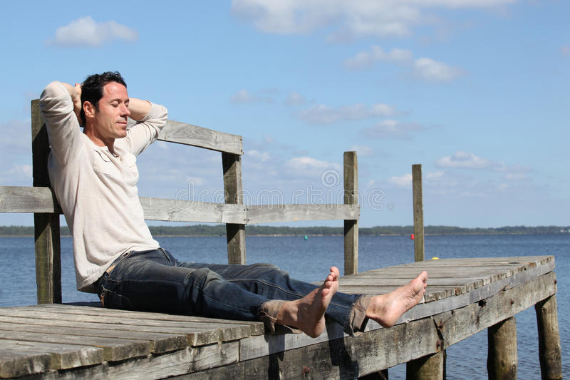 Man Sitting On A Jetty E Royalty Free Stock Photos