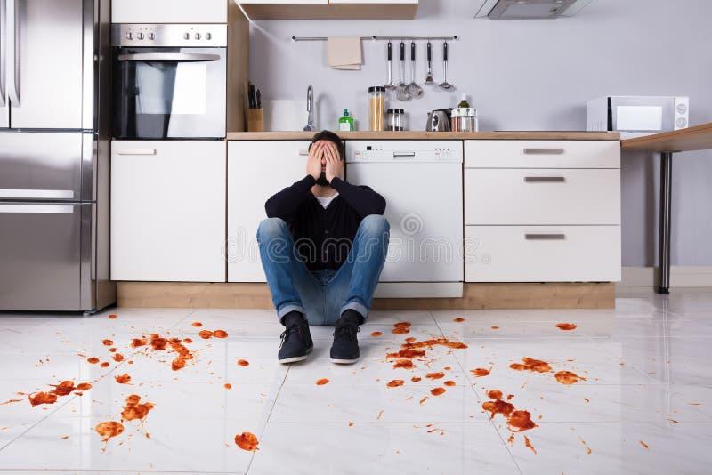 Man Sitting On Kitchen Floor With Spilled Food. Disappointed Young Man Sitting On Kitchen Floor With Spilled Food In Kitchen stock images