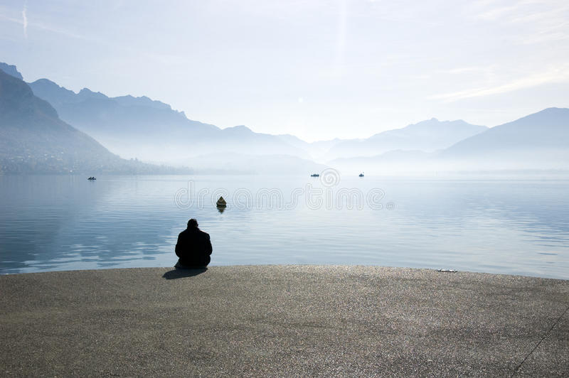 A man sitting at lake Annecy royalty free stock photography