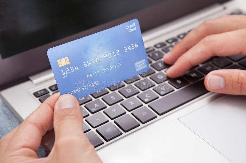 Man sitting with laptop and credit card shopping online. Young Man Sitting With Laptop And Credit Card Shopping Online stock photography