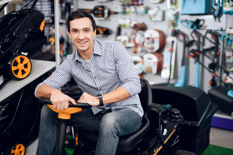 A man is sitting on a lawn mower. stock photos