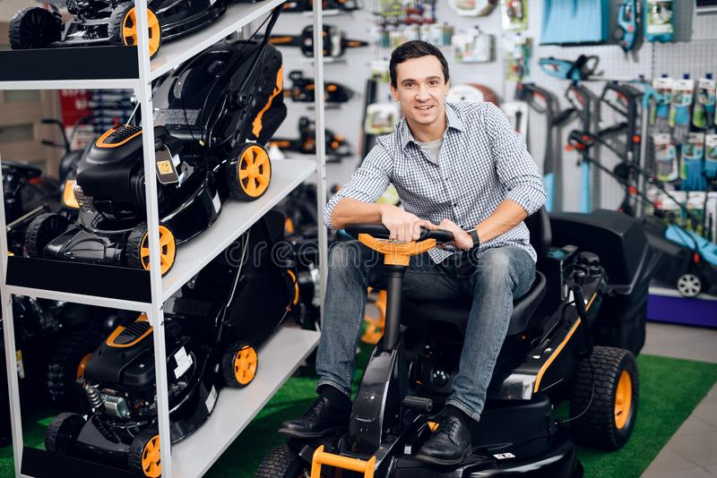 A man is sitting on a lawn mower. He is in the garden tools store. There are many tools for gardening here. The guy is smiling stock image