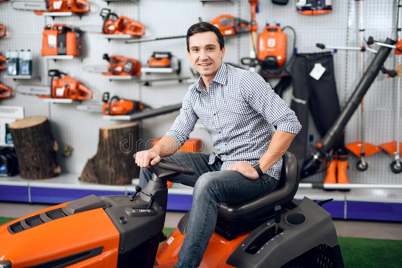 A man is sitting on a lawn mower. He is in the garden tools store. There are many tools for gardening here. The guy is smiling royalty free stock image