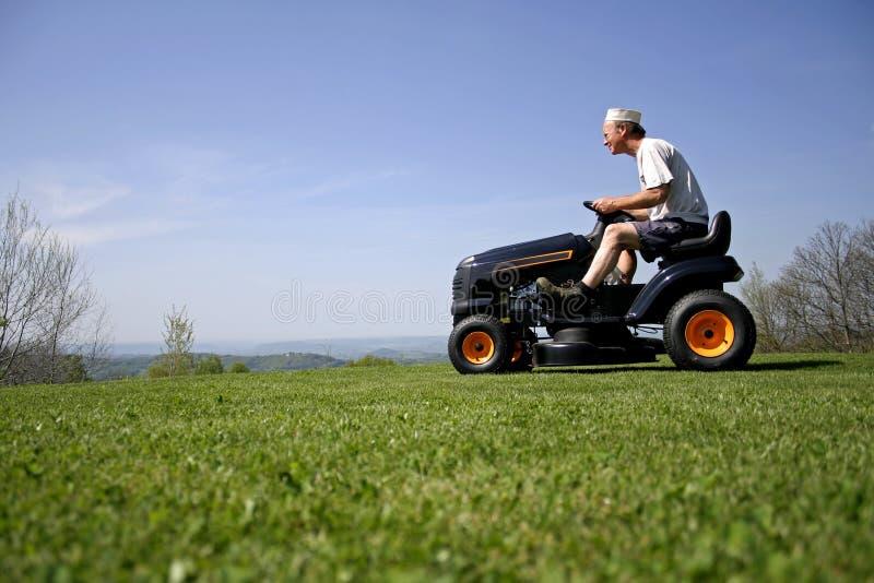 Man sitting on a lawnmower stock photos