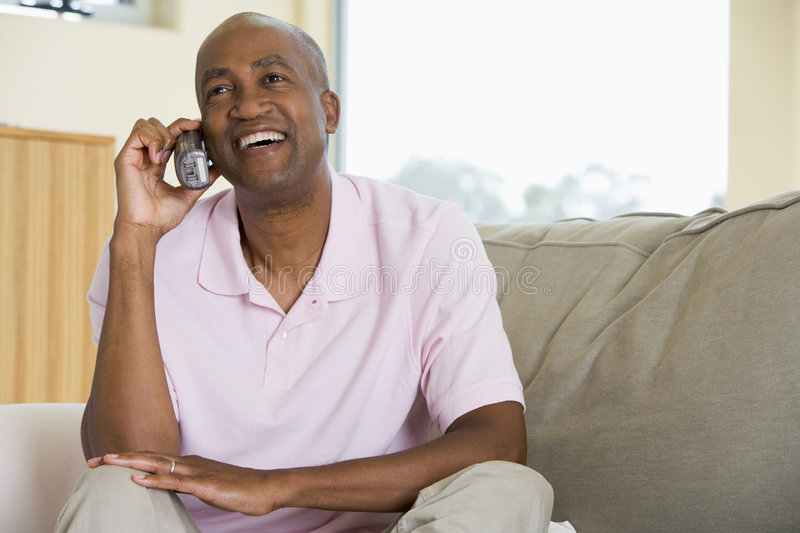 Man sitting in living room using telephone royalty free stock photo