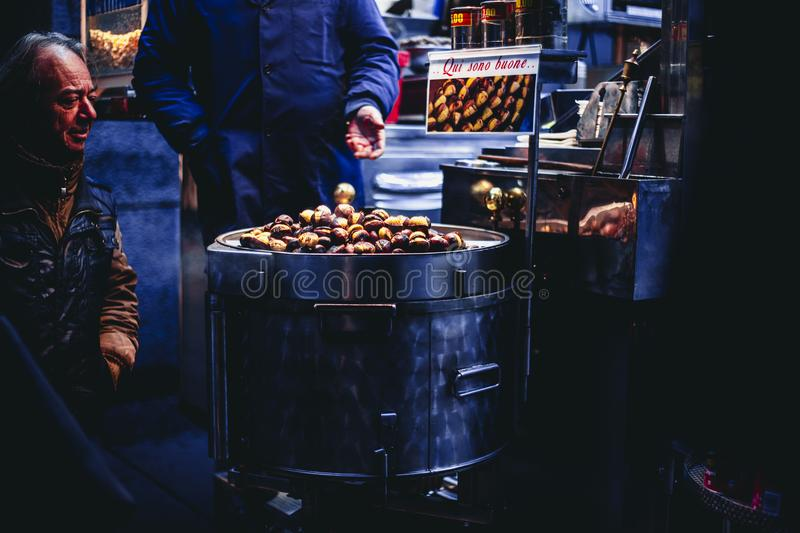 Man Sitting and Looking on Chestnuts stock images