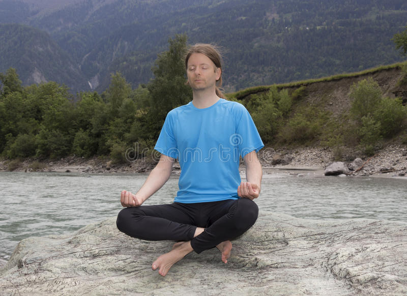 Man sitting in Lotus pose and meditating by a river royalty free stock photos