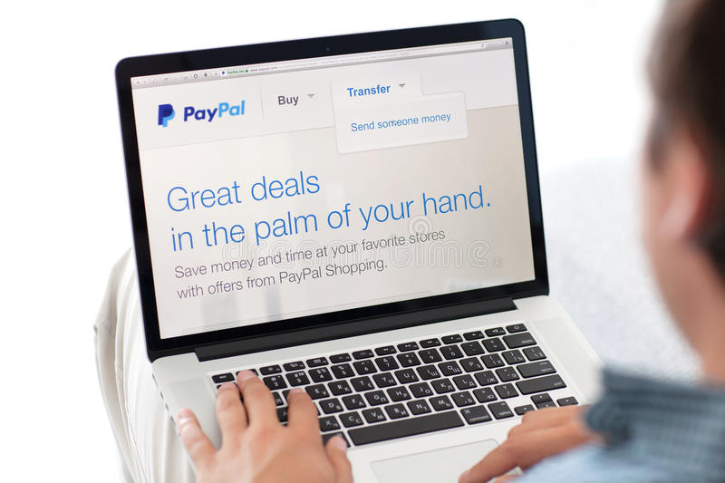Man sitting at the MacBook retina with site PayPal on the screen. Simferopol, Russia - July 13, 2014: PayPal the largest operator of electronic money it was royalty free stock images