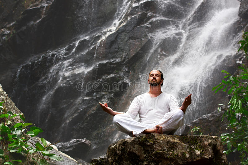 Man sitting in meditation yoga on rock at waterfall in tropical royalty free stock images