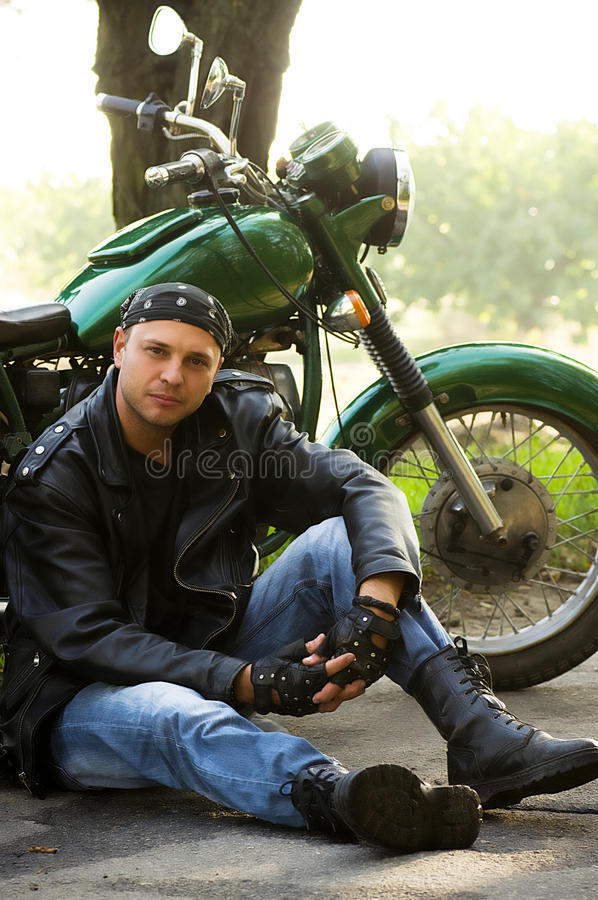 Man Sitting By Motorcycle Stock Images
