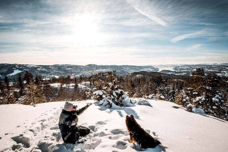 Man sitting near a dog Holding a Camera While Taking Picture of the Landscape stock photography